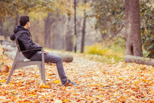 Young Man Sitting On A Bench In A Park In Autumn