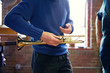 Midsection of man holding trumpet while working in workshop