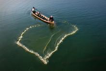 High Angle View Of Men Fishing At Sea