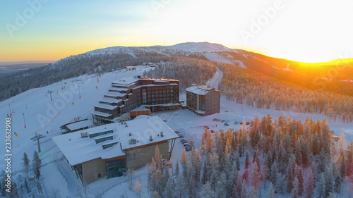 AERIAL: Flying around hilltop skiing resort surrounded by ski slopes in winter Tableau sur Toile