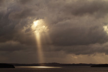 Sunlight Emitting From Cloudy Sky On Sea