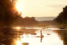 Distant View Of Woman Kneeling On Rocks In Lake During Sunrise