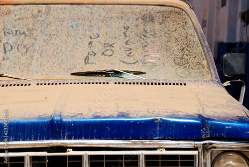 Ancient car windshield rendered opaque by sand and dust  Old pick-up