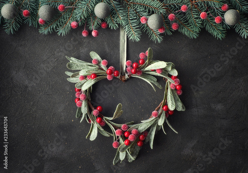 Fototapeta Heart-shaped mistletoe Christmas wreath and festive garland on dark background