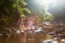 Couple Holding Hands While Crossing Stream In Forest