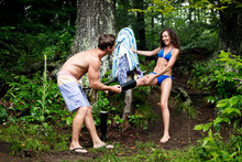 Man Removing Woman's Boot While Standing By Tree In Forest
