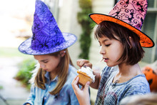 Girls Wearing Witch's Hats Decorating Muffin During Halloween Party