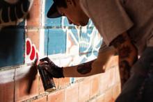 Side View Of Man Spraying Graffiti On Brick Wall