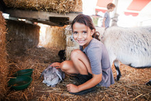 Portrait Of Girl Stroking Rabbit At Shed