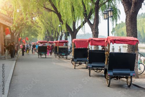 Fototapeta  Tourists riding Beijing traditional rickshaw in old China Hutongs in Beijing, China