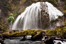 Hiker Looking At Idyllic Waterfall While Standing In Forest