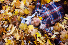 Overhead View Of Boy Lying On Fallen Dry Leaves At Yard