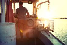 Rear View Of Fisherman Sailing Trawler In Sea During Sunset