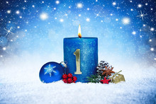First Sunday Of Advent Blue Candle With Golden Metal Number Red Decoration One On Wooden Planks In Snow Front Of Silver Panorama Bokeh Background