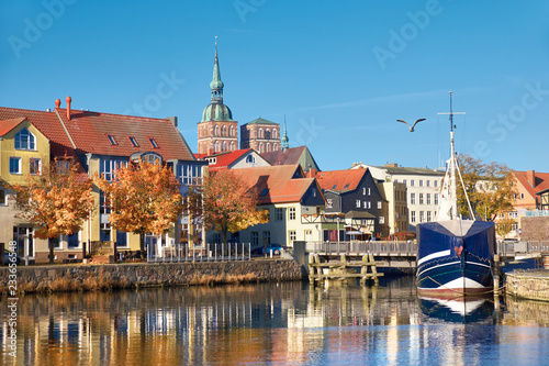 Docked sail boats and houses reflecting in channel with brick towers of Stralsund, Germany