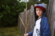 Portrait Of Boy Holding Stick Standing Fence