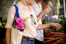 Midsection Of Woman Carrying Flowers Bouquet Buying Carrots With Friend In Market