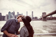Couple kissing while standing by railing against East River in New York City