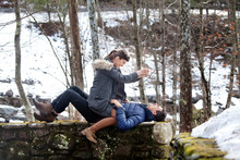 Playful Couple On Retaining Wall In Forest