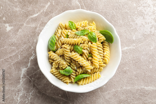Plate of delicious basil pesto pasta on table, top view