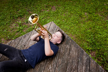 High Angle View Of Boy Playing Trumpet Lying On Porch