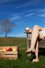 Low Section Of Woman Eating Apple While Sitting On Chair