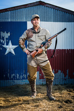 Portrait Of Hunter With Rifle Standing On Field Against Texas Flag