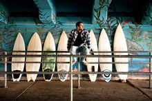Thoughtful Man Sitting On Railing Against Surfboards In Graffiti Tunnel