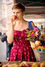Woman Smelling Apples While Carrying Flowers Bouquet In Market
