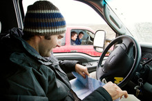 Man Reading Map While Traveling In Car With Friends In Background During Winter