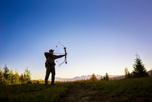 Hunter Hunting With Bow And Arrow While Standing On Field Against Clear Sky