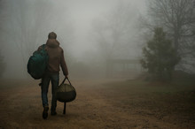 Rear View Of Man With Backpack Walking In Fog On Field