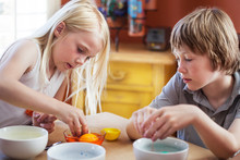 Brother And Sister Coloring Easter Eggs On Table At Home