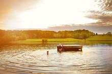 Boys Enjoying By Floating Platform On Lake Against Sky At Sunset