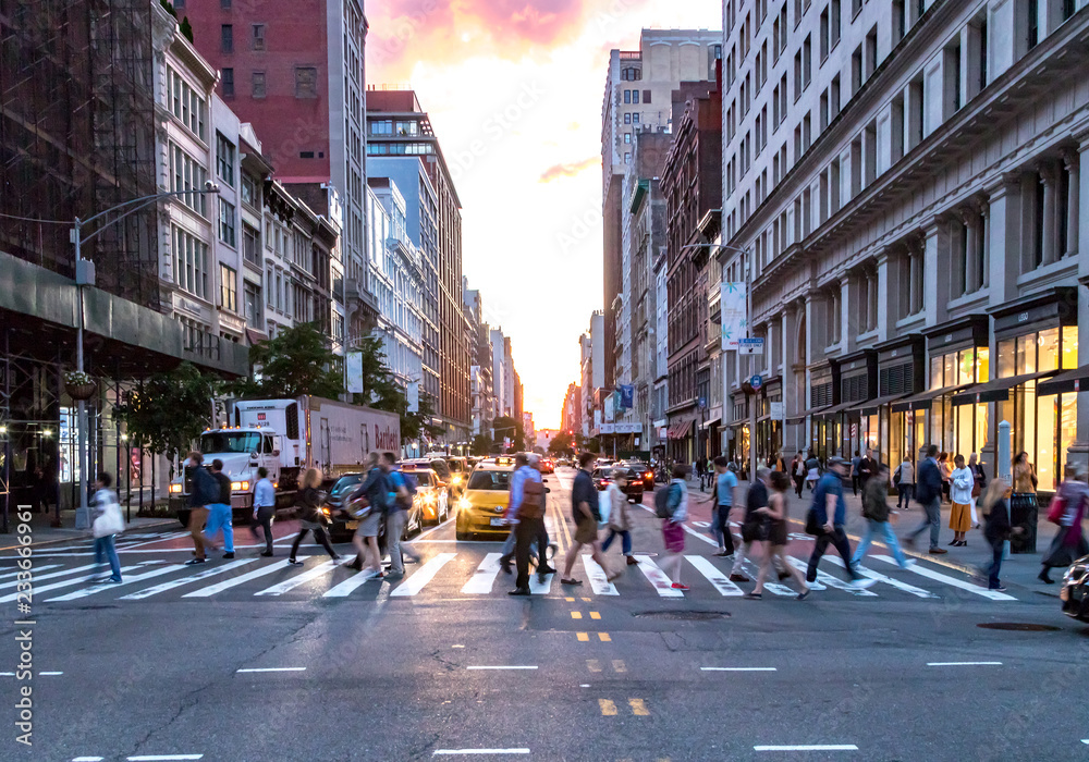 Fototapeta NEW YORK CITY - JUNE, 2018: Crowds of diverse people cross the busy intersection on 23rd Street and 5th Avenue in Manhattan with rush hour traffic in the background.