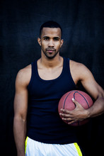 Portrait Of Confident Sportsman Holding Basketball While Standing Against Black Wall