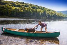 Man Stroking Dog Standing In Canoe