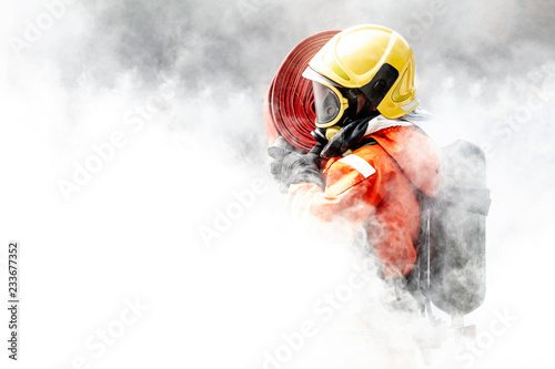 Photographie Firefighter in the midst of fire and smoke.