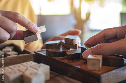 Fototapety, obrazy: Closeup image of two people playing and building round wooden puzzle game