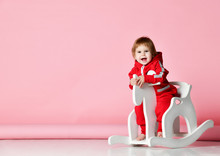 Toddler Baby Girl Is Riding Swinging On A Rocking Chair Toy Horse Over Light Pink