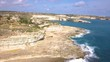 The dry landscape of Malta at the rocky coast. Aerial view of St. Peter's Pool. Waves crash onto the shoreline. Bright blue sky. Drone backing. ZOOM OUT.