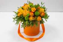 Bright Bouquet Of Orange Roses And Green Flowers In An Orange Box For Hats On A Light Background