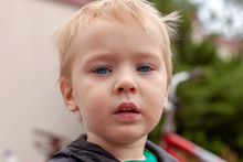 Close Up Portrait Of Cute Caucasian Baby Boy With Serious Expression In Blue Eyes. Fair Hair. Strong Emotions. Outdoors, Green Background, Copy Space.