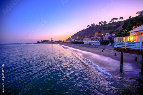 Scenic coastal landscape with Santa Monica Mountains and Surfrider Beach at dusk iluminated by night. Malibu, California, United States. Californian West Coast travel. Copy space.