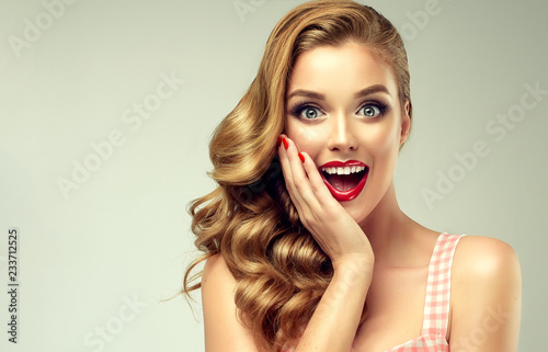 Fotografia, Obraz  Woman with red lips and nails surprise holds cheeks by hand