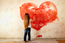 The Child Painted The Wallpaper In The Room With Red Paint. Paint The Walls With A Roller. The Girl Painted A Heart On The Wall. Valentine's Day, A Gift To Parents.