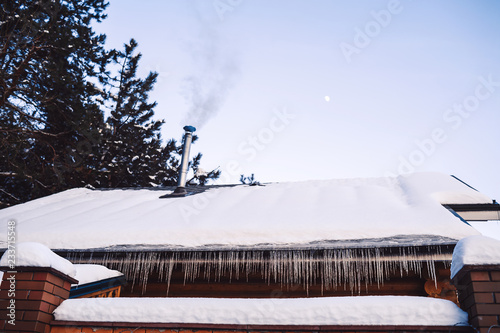 The roof of a wooden house covered with snow and icicles