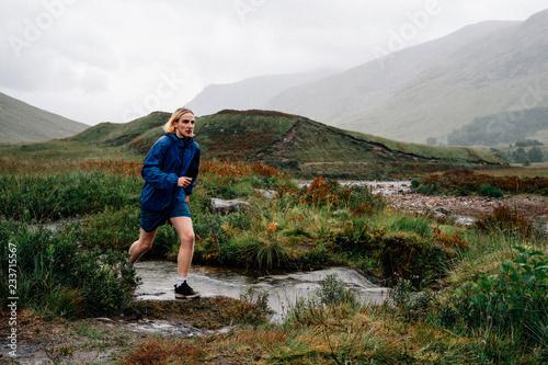 Fotografie, Obraz  Man jogging alone in rough terrain