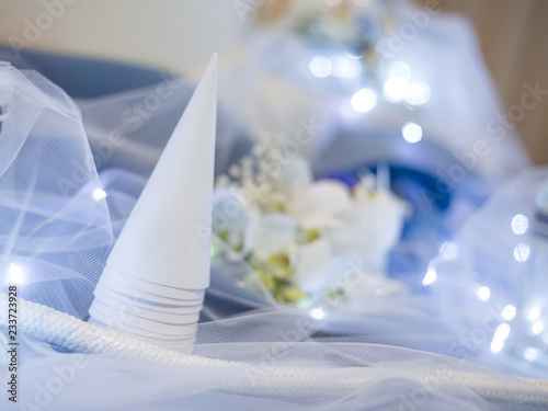 White cone for confetti on blue table decorated for ceremony