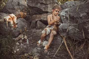 Caveman, manly boy making primitive stone weapon. Funny young primitive boy outdoors near bonfire. Evolution survival concept. Calm boy outside sitting at his rocky settlement. Prehistoric tribal man